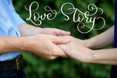 Man is holding a woman hands for a walk in a summer park and vintage text Love story. Calligraphy lettering hand draw Royalty Free Stock Images