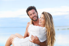 Man holding woman in his arms under a blue sky on seaside Stock Photos