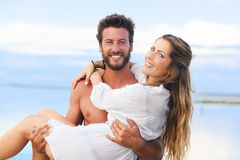 Man holding woman in his arms under a blue sky on seaside  Royalty Free Stock Photos