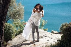 Man holding woman in his arms wrapped around her waist and she is holding on to him, standing near sea in Greece. royalty free stock photo