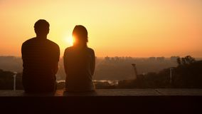 Couple observing the sundown. Man holding woman. lady puts her head on his shoulder stock footage