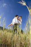 Man holding woman in rural field royalty free stock photography