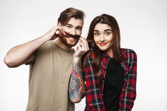 Man holding woman`s hair as it is moustache, smiling happily. Stock Image