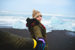 Man Holding Woman`s Hand at Iceland Beach. Man holding woman`s hand at winter Iceland beach Royalty Free Stock Photo