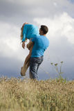 Man holding woman up in air Stock Images