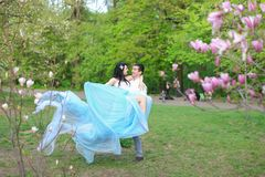 Man holding woman wearing blue dress in park near magnolia tree. Man holding women wearing blue dress in park near magnolia tree. Concept of spring and nature royalty free stock image