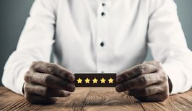 Man holding wood block with five stars. Increase rating royalty free stock images