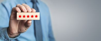 Man holding wood block with five stars. Increase rating royalty free stock photos