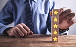 Man holding wood cube with five stars. Increase rating royalty free stock photo