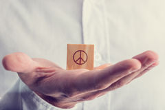 Man holding a wooden block with the peace sign Stock Images