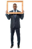Man holding wooden picture frame, looking down Royalty Free Stock Photo