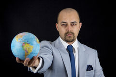 Man holding world in his hand, save the planet. Isolated on black background Royalty Free Stock Image
