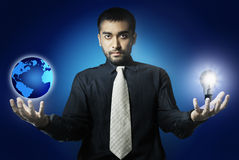 Man holding world and light bulb Royalty Free Stock Image