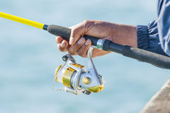 Man holding yellow fishing rod Royalty Free Stock Photo