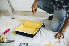 Man Holding Yellow Paint Roller