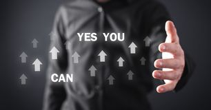 Man holding Yes You Can text with arrows. Motivation, Business, Development stock photo