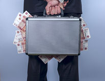 Man Holds A Suitcase Full Of Money Behind The Back Stock Photo