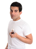 Man holds aftershave or men's fragrance Stock Photos