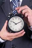 Man holds a alarm clock royalty free stock photo