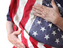 Man holds American flag close to his body Stock Image