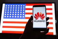 A man holds an android-smartphone. PERAK, MALAYSIA - MAY 24, 2019: A man holds an android-smartphone that shows the Huawei logo in front of the USA flag. Google stock photography