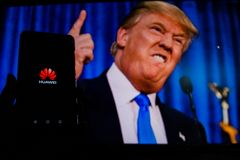 A man holds an android-smartphone that shows the logo for the google play store in front of the picture of Donald Trump. PERAK, MALAYSIA - MAY 24, 2019: A man stock photo