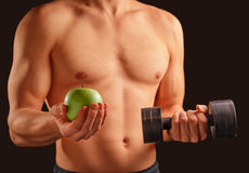 Man holds apple and dumbbell Royalty Free Stock Images