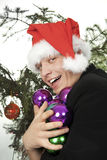Man holds an armful of fur-tree toys Stock Photos