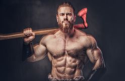 A man holds axe over dark grey background. Stock Images