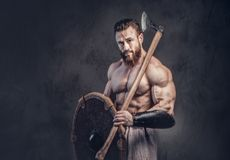 A man holds axe over dark grey background. Royalty Free Stock Photos