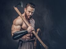 A man holds axe over dark grey background. Royalty Free Stock Photo
