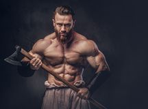 A man holds axe over dark grey background. Royalty Free Stock Photography