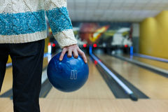 Man holds ball at bowling lane, cropped image. Unrecognizable man holds ball, prepare to throw it to bowling lane, closeup. Player plays active game. Cropped Royalty Free Stock Photos