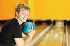Man holds ball and prepares to throw in bowling. Young man wearing in black t-shirt holds blue ball and prepares to throw in bowling club Royalty Free Stock Photo