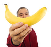 Man holds banana in front of his face Stock Photo