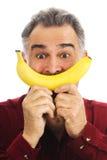 Man holds banana to face, imitating smile royalty free stock photo