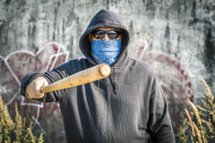 Man holds a baseball bat forward on a wall Stock Photography