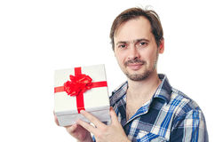 The man holds a beautiful gift in hand. The man with a beard holds a white box with a red bow in hand and smiles royalty free stock images