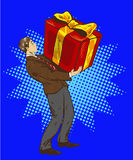 Man holds big gift box. Vector illustration in retro comic pop art style. A guy with christmas or birthday present Royalty Free Stock Image
