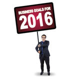 Man holds billboard with business goals for 2016. Image of young businessman standing in the studio while holding a big board with a text of business goals for Royalty Free Stock Photography