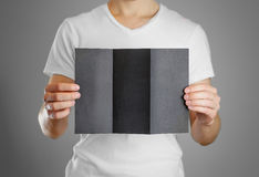 A man holds a black paper in his hand. Shows a blank flyer.  Stock Photo