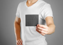 A man holds a black paper in his hand. Shows a blank flyer.  Royalty Free Stock Image