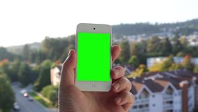 Man holds a blank smart phone with a green screen for your own custom content. stock video footage