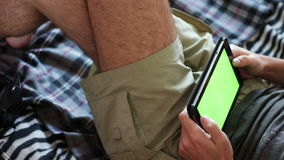 Man holds a blank tablet PC with a green screen on sofa. Man is Laying on Couch at Home and Watch on Tablet with Green Screen,man holds a blank tablet PC with a stock video footage