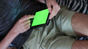 Man holds a blank tablet PC with a green screen on sofa stock footage