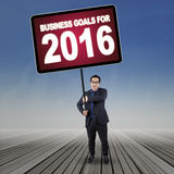 Man holds a board with business goals for 2016 outdoors. Young entrepreneur standing outdoors while holding a big board with a text of business goals for 2016 Stock Photo