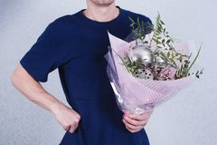 A man holds a bouquet of flowers and ladles. concept of patriarchal society and gender inequality. Sexism and feminism.  stock image