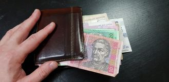 A man holds brown leather wallet full with hryvnia royalty free stock images
