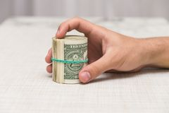 A man holds a bundle of money in his hand tied with an elastic band Royalty Free Stock Photos