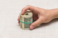 A man holds a bundle of money in his hand tied with an elastic band Royalty Free Stock Image